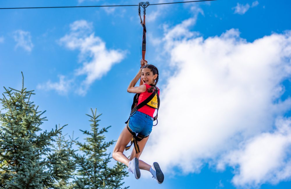 A girl smiling and hanging on a zipline