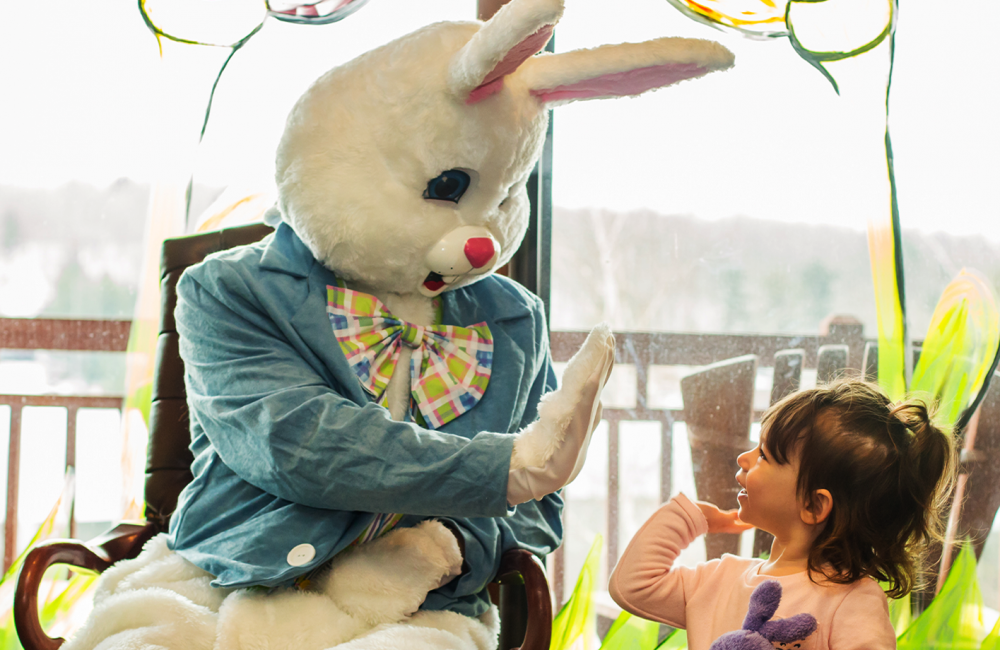 a little girl smiling and giving a high five to the easter bunny