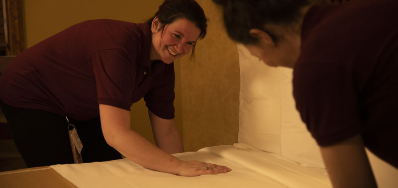 Two smiling employees making a bed