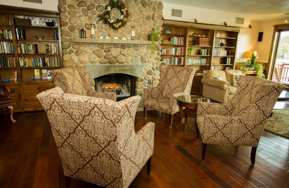 4 chairs set up infant of a stone fireplace with a roaring fire inside