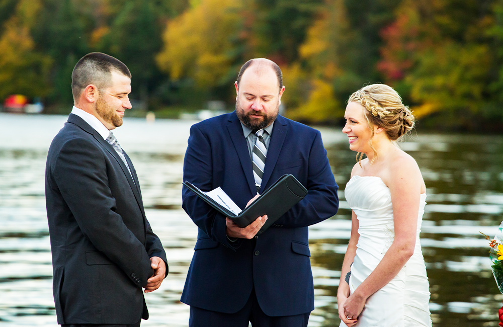 people getting married in front of the lake in the fall
