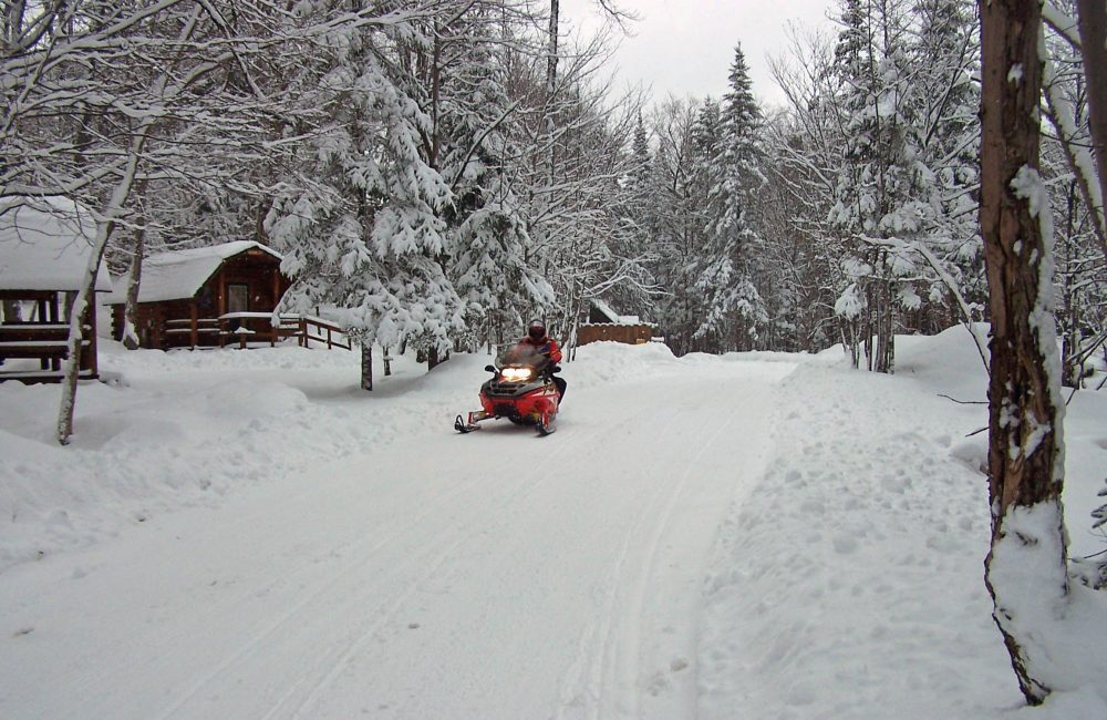 A snowmobiler driving pas wooden cabins on a trail with trees with freshly fallen snow on them around him