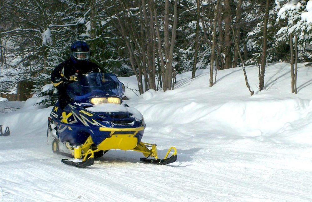 A snowmobiler snowmobiling on a trail